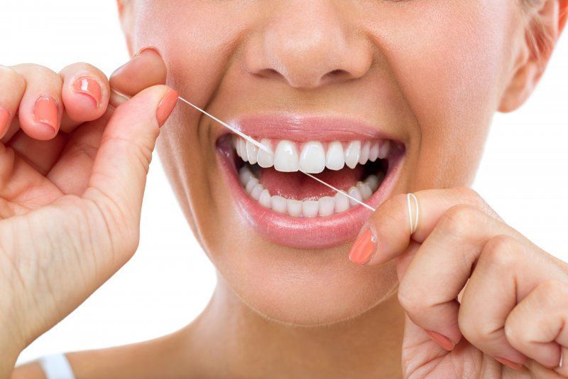 A woman flossing.