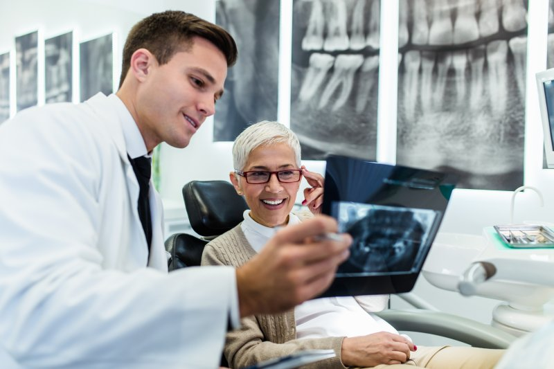 A dentist showing a patient an X-ray.