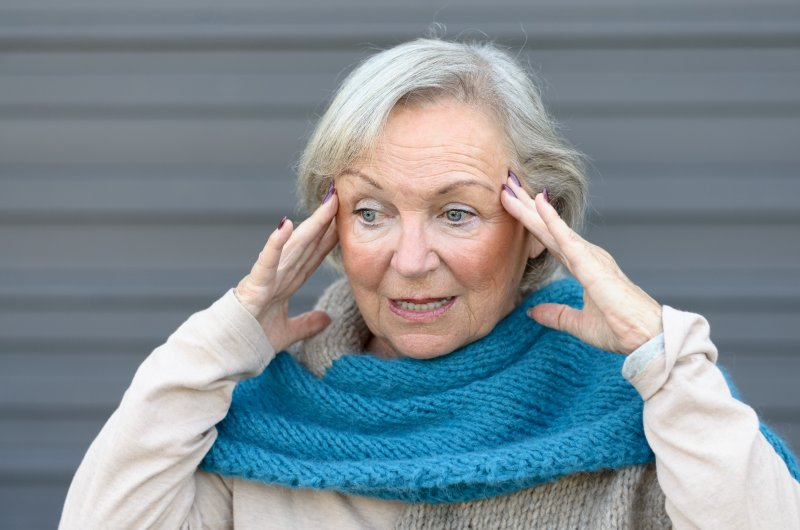 Older woman with gum disease in Frisco holding her head.