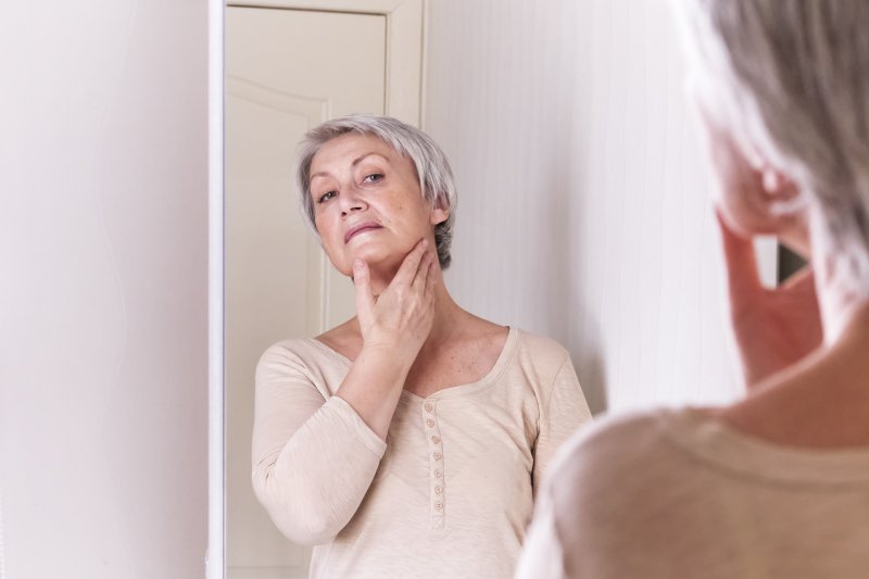 Woman examining her gum disease and facial shape in Frisco