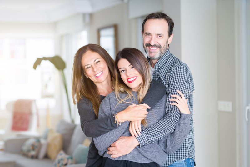 Family members hugging after preventing gum disease in Frisco